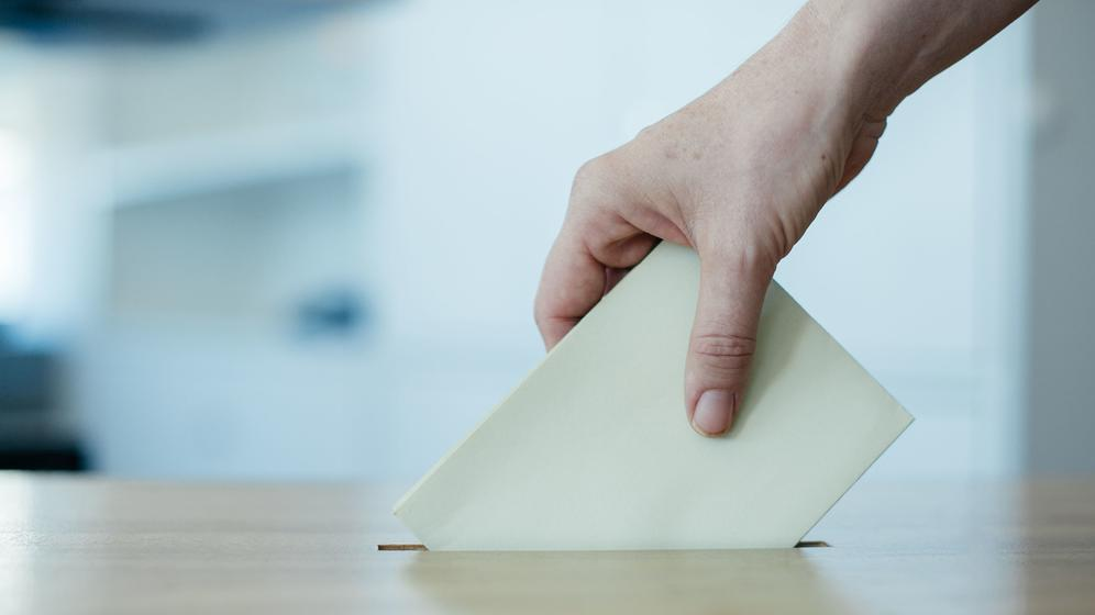 Eine Hand wirft einen Wahlzettel in eine Wahlurne. | Bild:BR-Bild