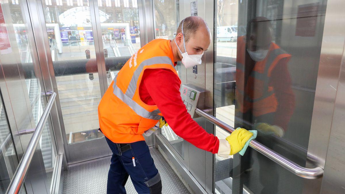 Ein Mitarbeiter desinfiziert nach einer Reinigung einen Fahrstuhl