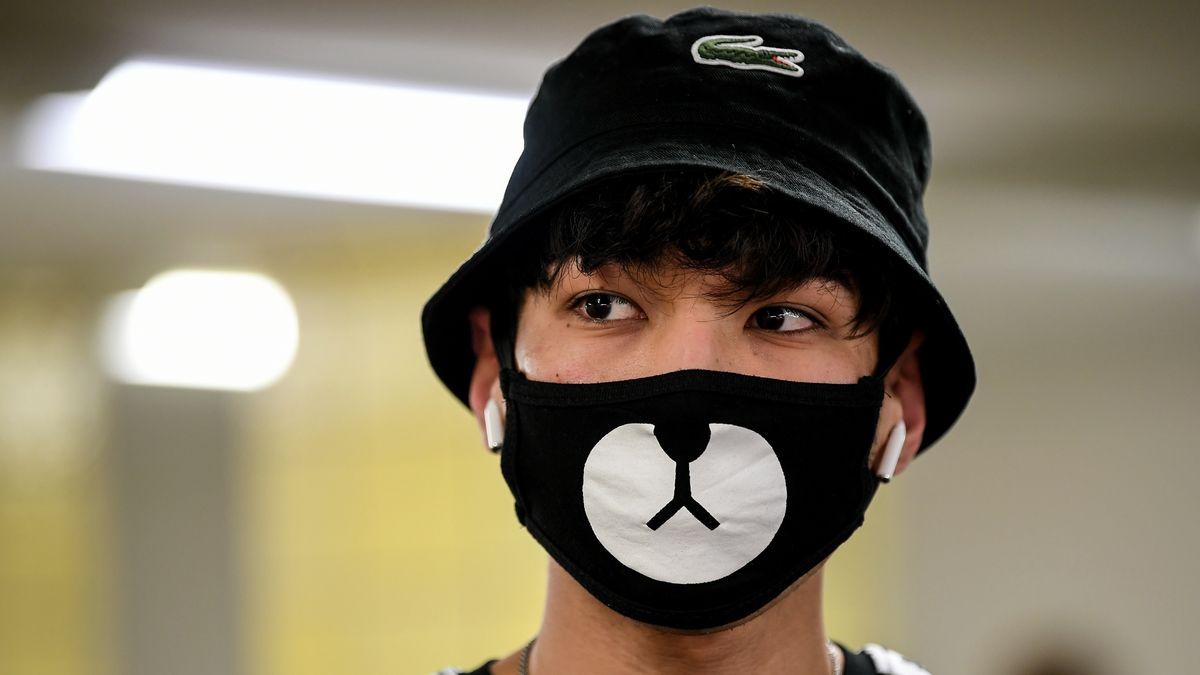 Ein junger Mann trägt einen Nasen-Mund-Schutz mit Panda-Design