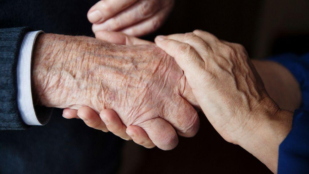 Pflegerin hält die Hand eines Senioren.