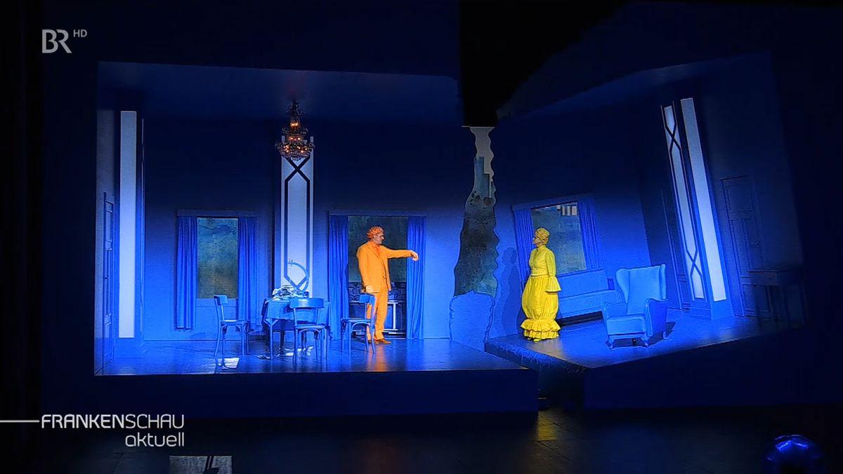 Zwei Schauspieler agieren auf der in blaues Licht getauchten Bühne im Theater Hof.