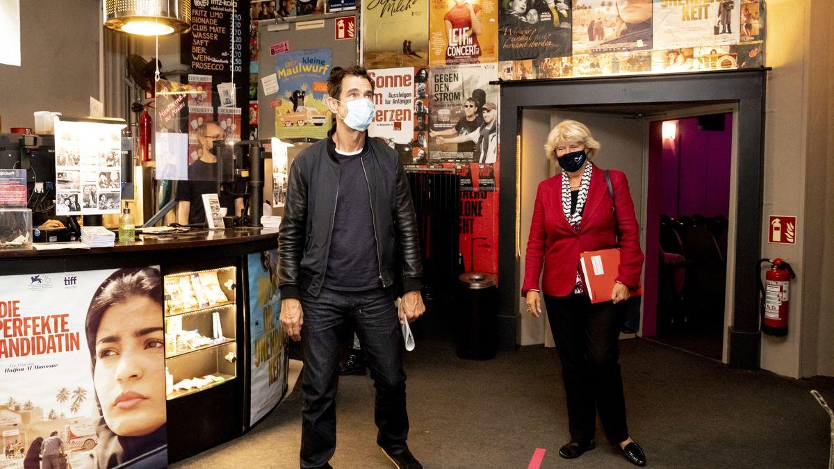 Monika Grütters und Regisseur Tom Tykwer stehen im Eingangsbereich eines Kinos. Im Hintergrund sind Filmposter zu sehen.