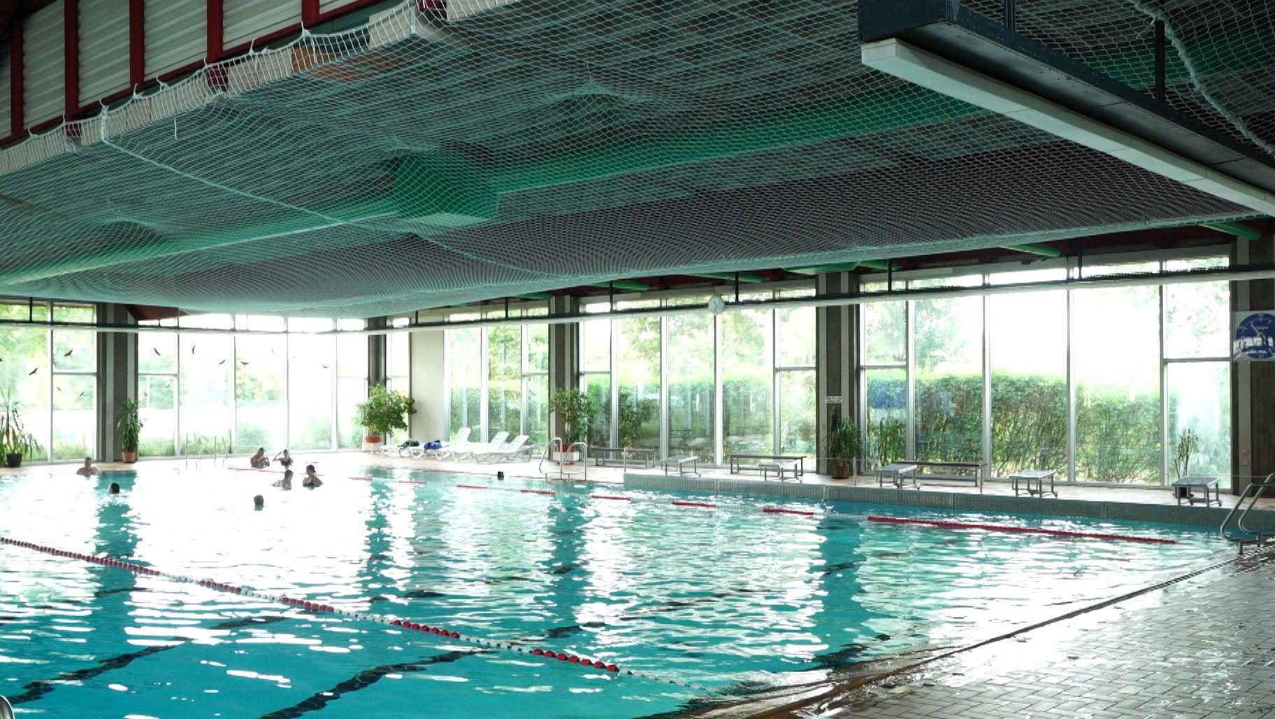 Das Schwimmbecken im Hallenbad Haunstetten. Darüber weißte Netze zum Schutz der Schwimmer