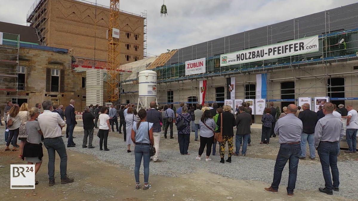 Gäste des Richtfests stehen vor der eingerüsteten Stadthalle, vor der ein gelber Kran aufgebaut ist.