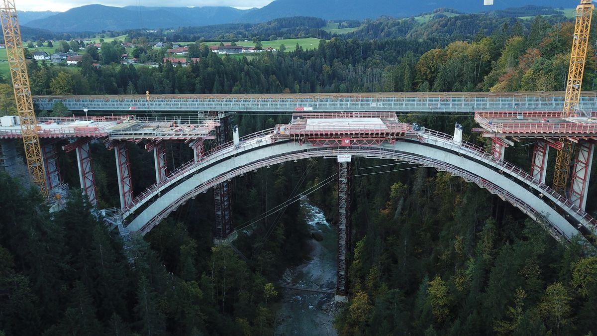 Die Echelsbacher Brücke, eine gebogene Brücke tief über einer bewaldeten Schlucht, durch die die Ammer fließt. Im Hintergrund ein Dorf und Berge.