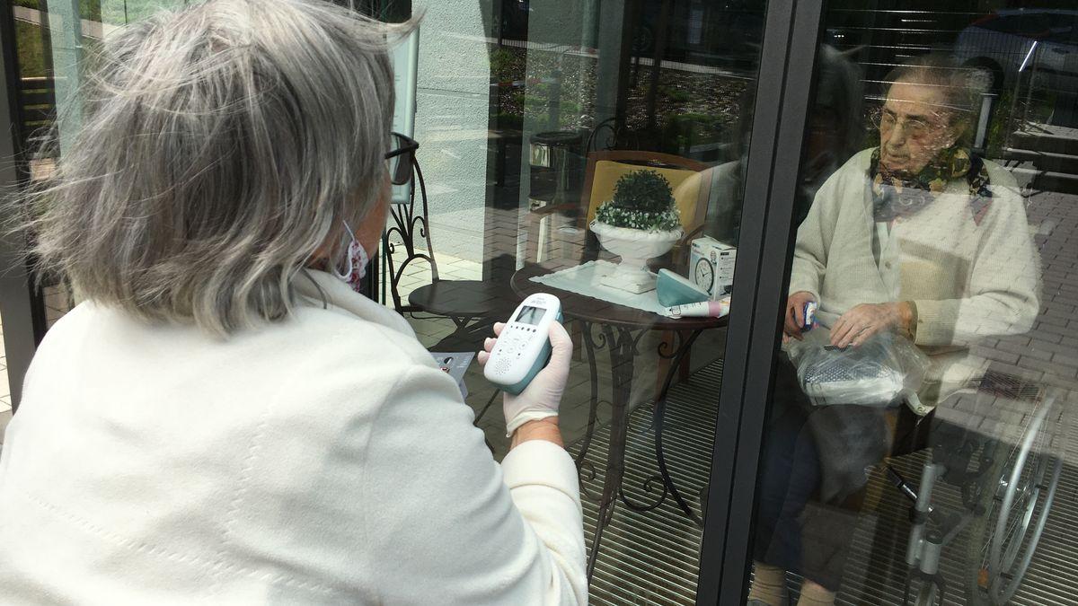 Angehörige stehen sich im AWO-Seniorenheim in Zeil am Main an geschlossener Glastüre gegenüber und kommunizieren über Babyphone.