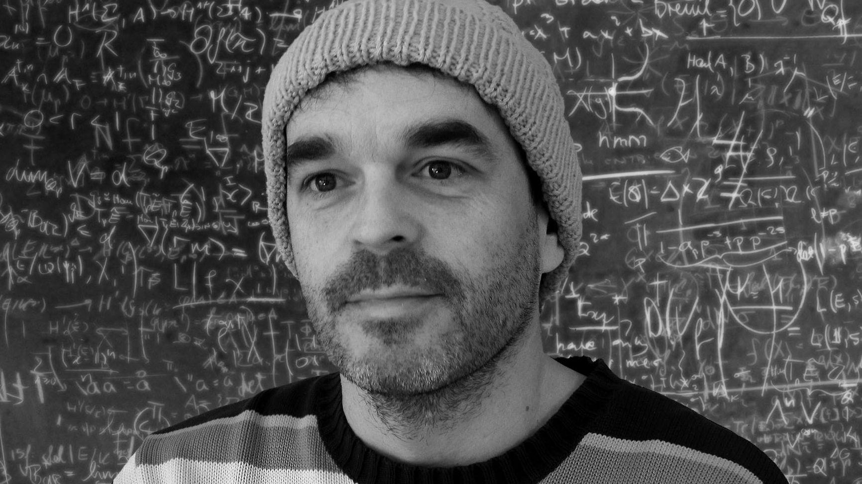 Schwarz-weiß Porträt von René Gisler vor einer Schultafel