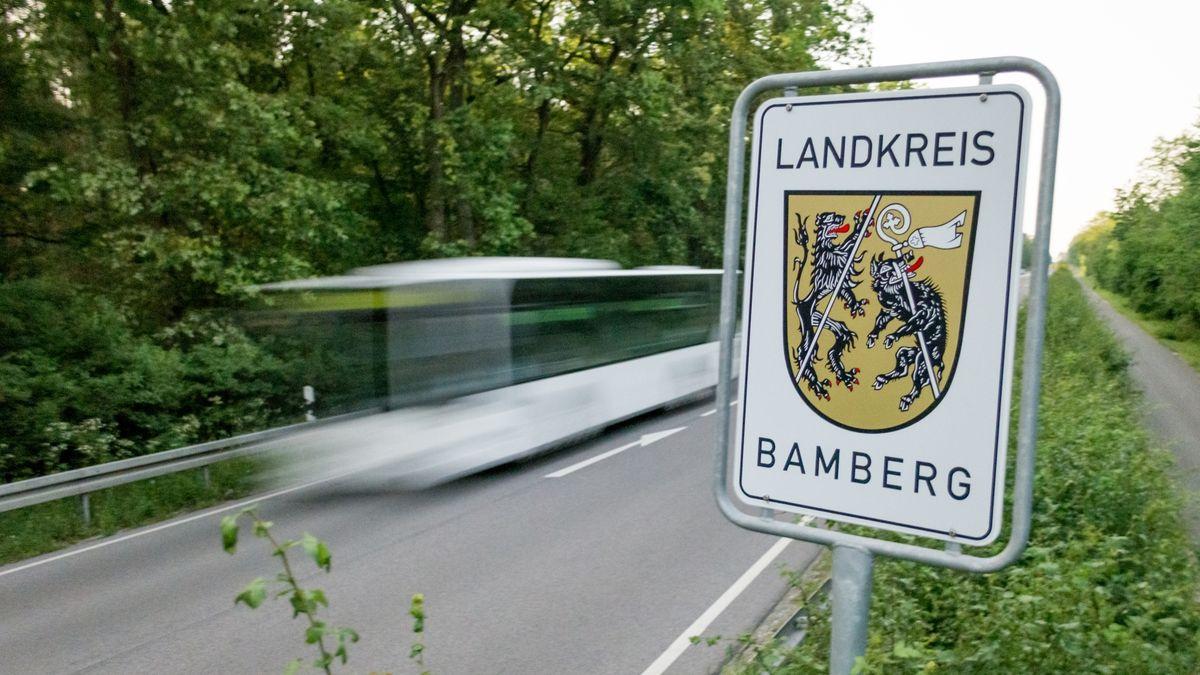 Ein Schild mit der Aufschrift Landkreis Bamberg steht an einer Straße. Dahinter fährt ein Bus.