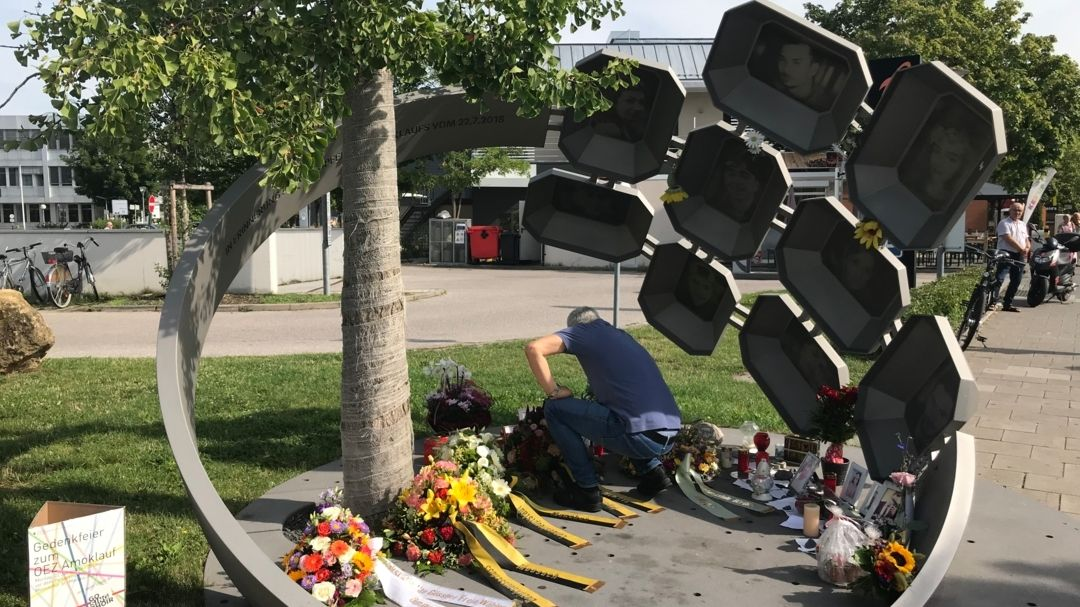 Kränze und Mann, der in der Hocke sitzt - im Denkmal zum Gedenken an den 3. Jahrestag des OEZ-Anschlags. Ein diagonal stehender Eisenring mit 9 Tafel , die an die Opfer erinnern
