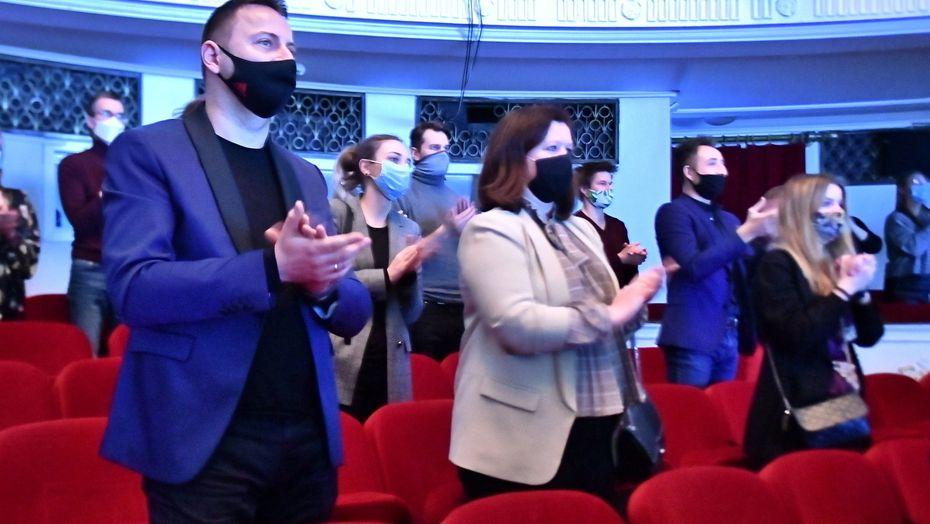 Klatschendes Publikum mit Masken in einem Theatersaal