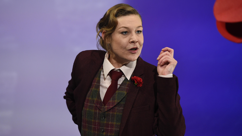 Die Schauspielerin Ewa Rataj als Ernst Toller: In weißem Hemd, mit Schlips, karierter Weste und bordeauxrotem Jackett, eine rote Blume am Revers.