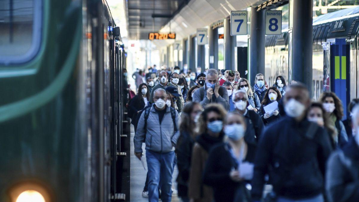 Italien, Mailand: Pendler mit Mundschutz gehen über einen Bahnsteig.