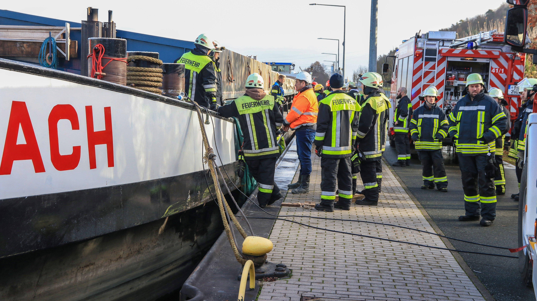 Feuerwehrleute stehen vor einem Schiff