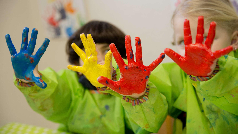 Kindergartenkinder halten ihre bunt bemalten Hände in die Luft.