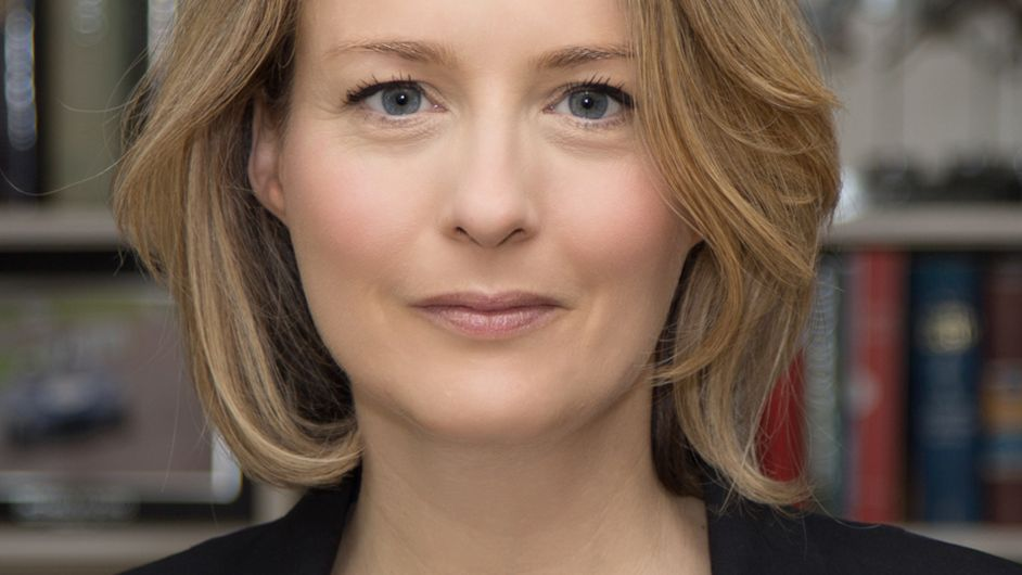 Autorin und Anthropologin Anna Machin blickt, vor einer Bücherwand stehend, freundlich in die Kamera