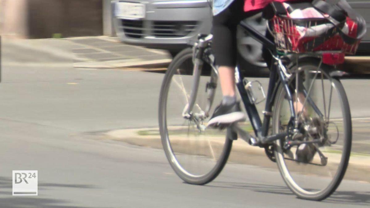 Eine Frau fährt mit dem Fahrrad auf einer Straße