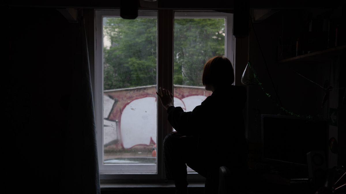 Eine Jugendliche sitzt in einem abgedunkelten Zimmer am Fenster (Symbolbild)