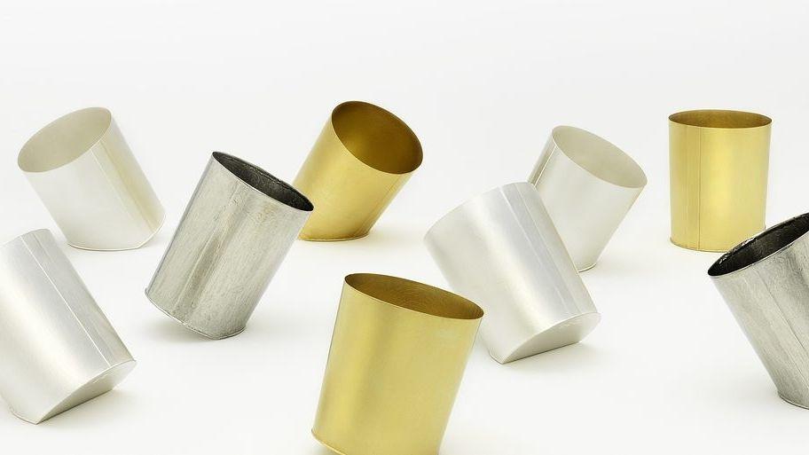 Goldene und silberne Becher mit schrägem Boden auf weißer Fläche, so dass es aussieht, als würden sie tanzen.