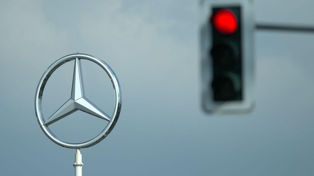 Eine rote Ampel ist neben dem Mercedes-Stern eines Werkes der Daimler AG zu sehen.