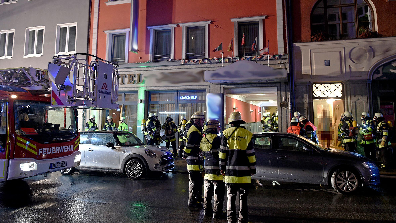 Einsatzkräfte der Feuerwehr stehen vor einem Hotel in der Landwehrstraße in München.