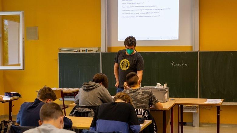 Schülerinnen und Schüler sitzen in ihrer Klasse, während ein Lehrer neben geöffneten Fenstern vor der Tafel steht.