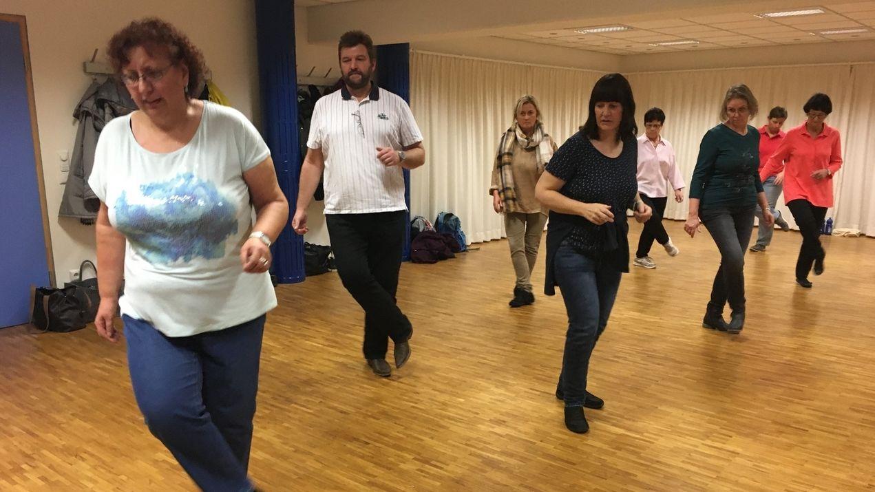Mehrere Frauen und ein Mann tanzen in Reih- und Glied.