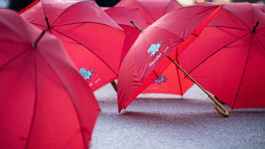 """Bayern, Anzing: Regenschirme mit der Aufschrift """"Handel ver.di"""" und dem Bild einer erhobenen Faust liegen bei einem Warnstreik vor einem Lager der Supermarktkette Lidl auf dem Asphalt."""