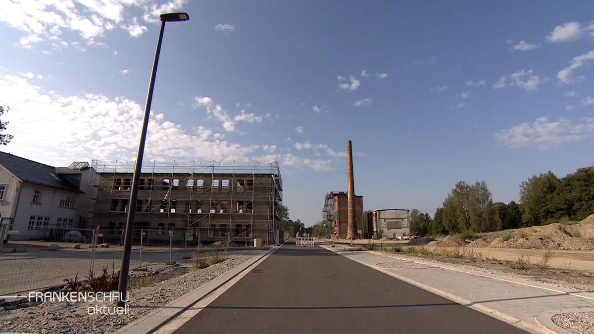 Neben einer Straße entstehen Bauplätze, im Hintergrund ein alter Fabrikschlot aus Bachstein.