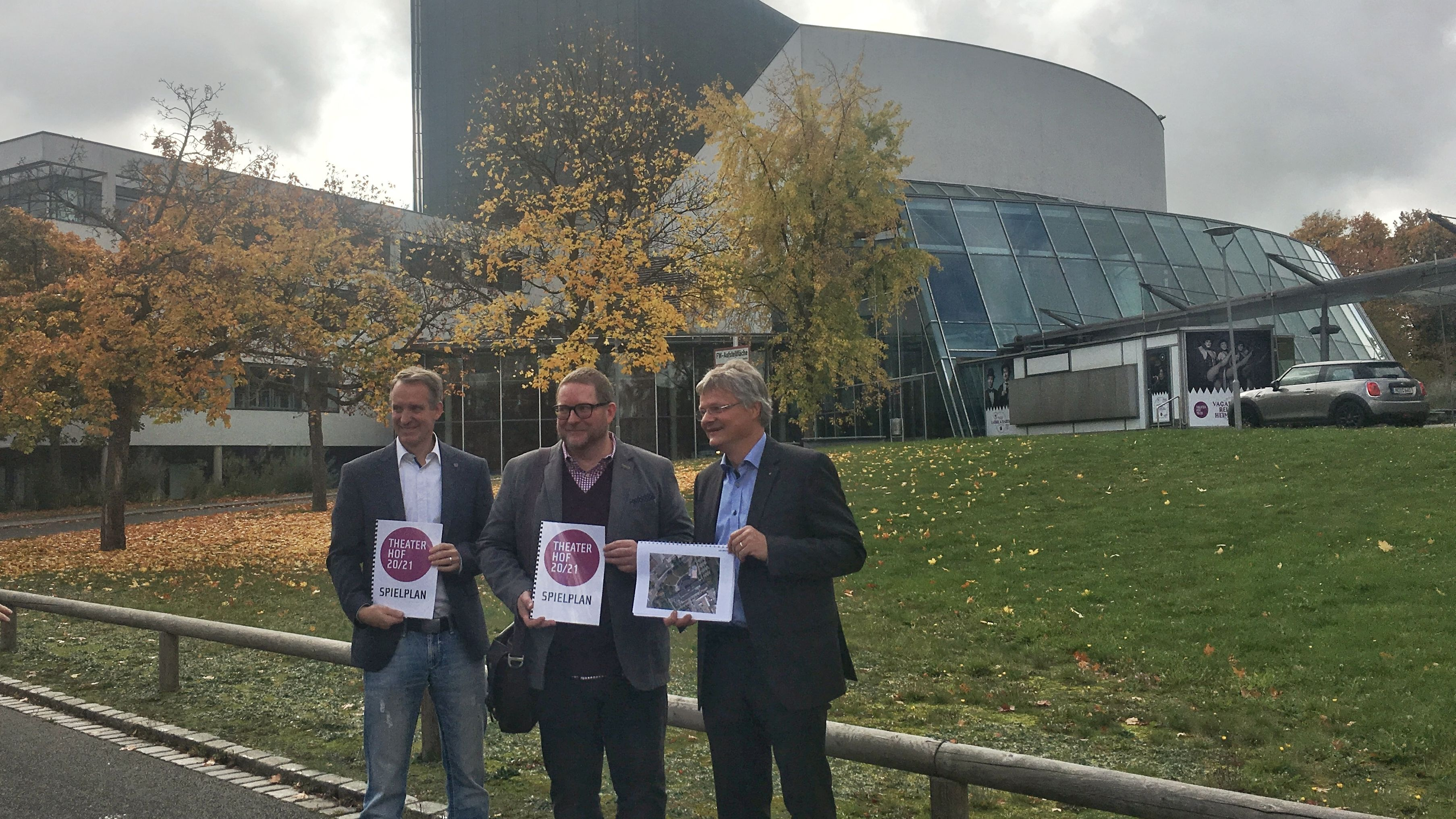 Geschäftsführer Florian Lühnsdorff, Intendant Reinhardt Friese und Kulturamtsleiter Peter Nürmberger mit dem Spielplan 2020/2021 vor der Freifläche vor dem Theater, die als Interimsspielstätte dienen soll.