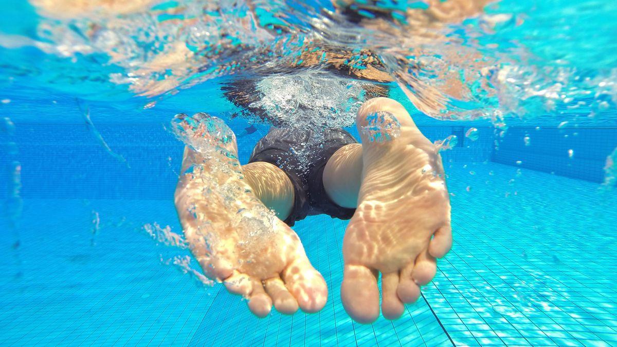 Ein Schwimmer im Schwimmbad von hinten. Im Wasser steigt der Harndruck beim Menschen.