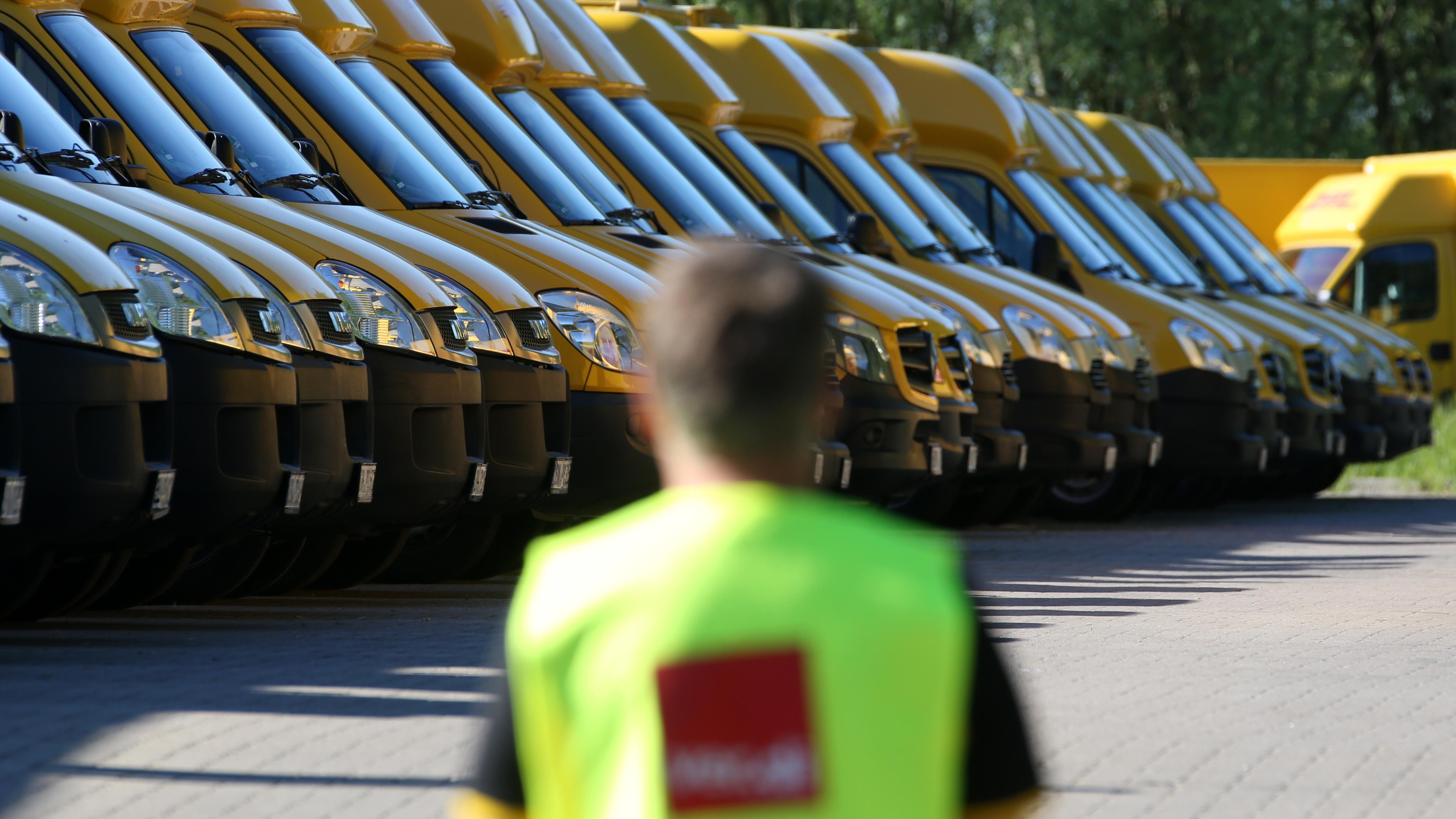 Ein streikender Mitarbeiter vor den DHL-Fahrzeugen