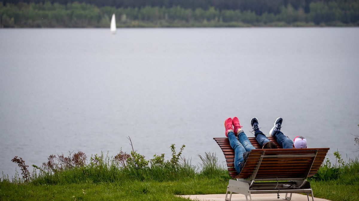 Zwei Ausflügler liegen auf einem Stuhl mit Blick auf den Brombachsee.