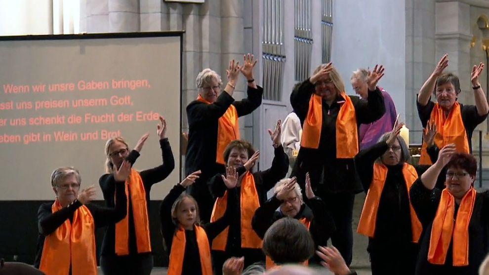 Die Mitglieder des Gebärdenchors Würzburg bei einem Konzert in einer Kirche.