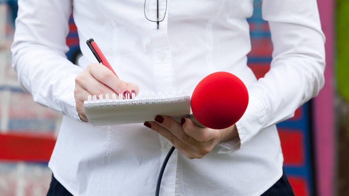 Eine Journalistin schreibt auf einem Notizblock und hält ein Mikrofon in der Hand.