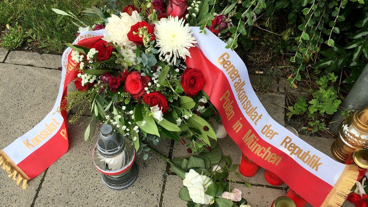 """Ein Blumengesteck mit roten Rosen und einer Schleife, auf der """"Generalkonsulat der Republik Polen in München"""" zu lesen ist."""