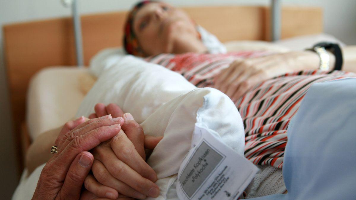 Eine ehrenamtliche Helferin hält die Hand einer sterbenden Bewohnerin, die in ihrem Bett im Christophorus Hospiz in München (Oberbayern) liegt, aufgenommen am 05.06.2008.