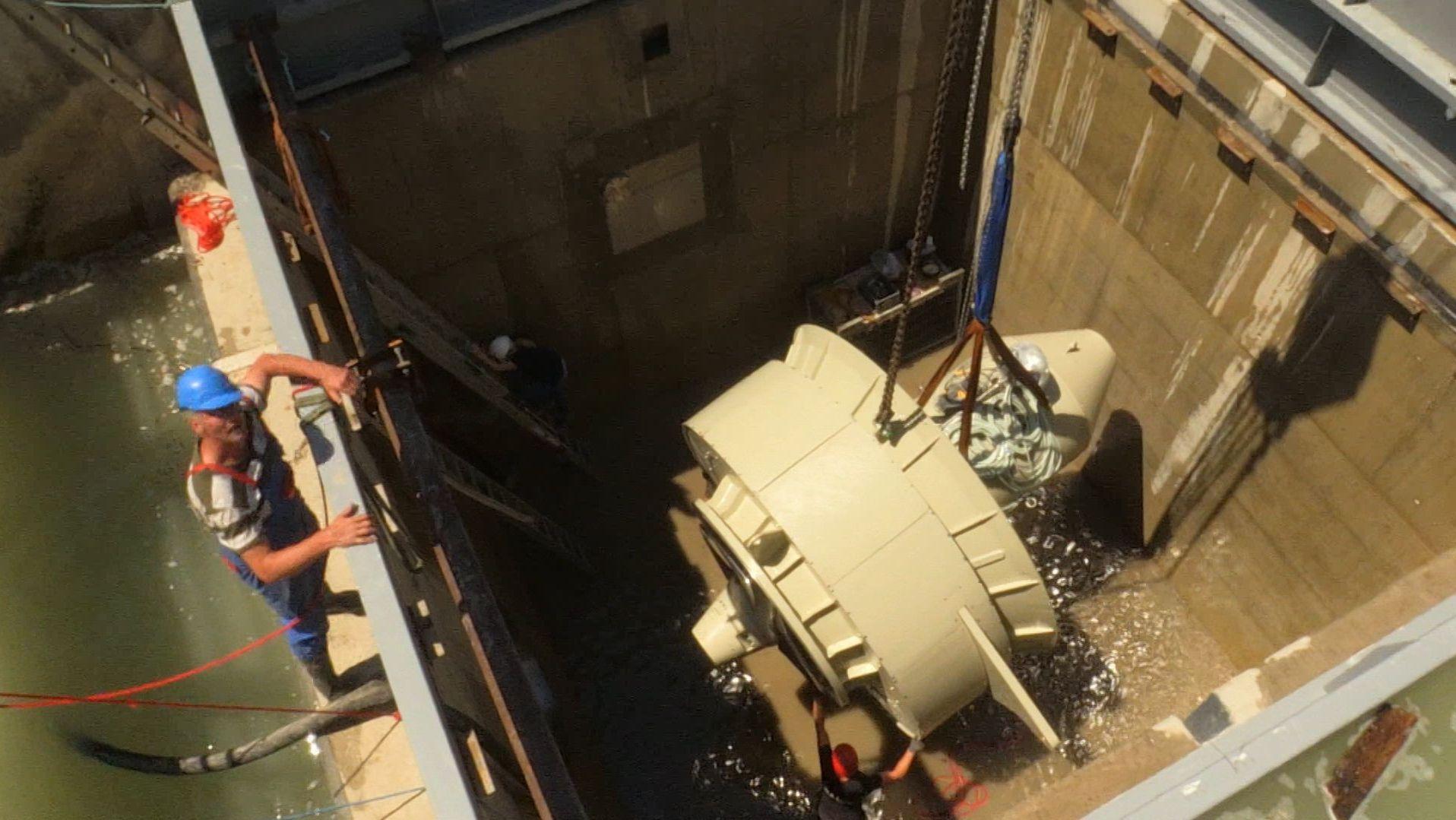Arbeiter beim Einheben der Turbine ins Wasserkraftwerk Großweil