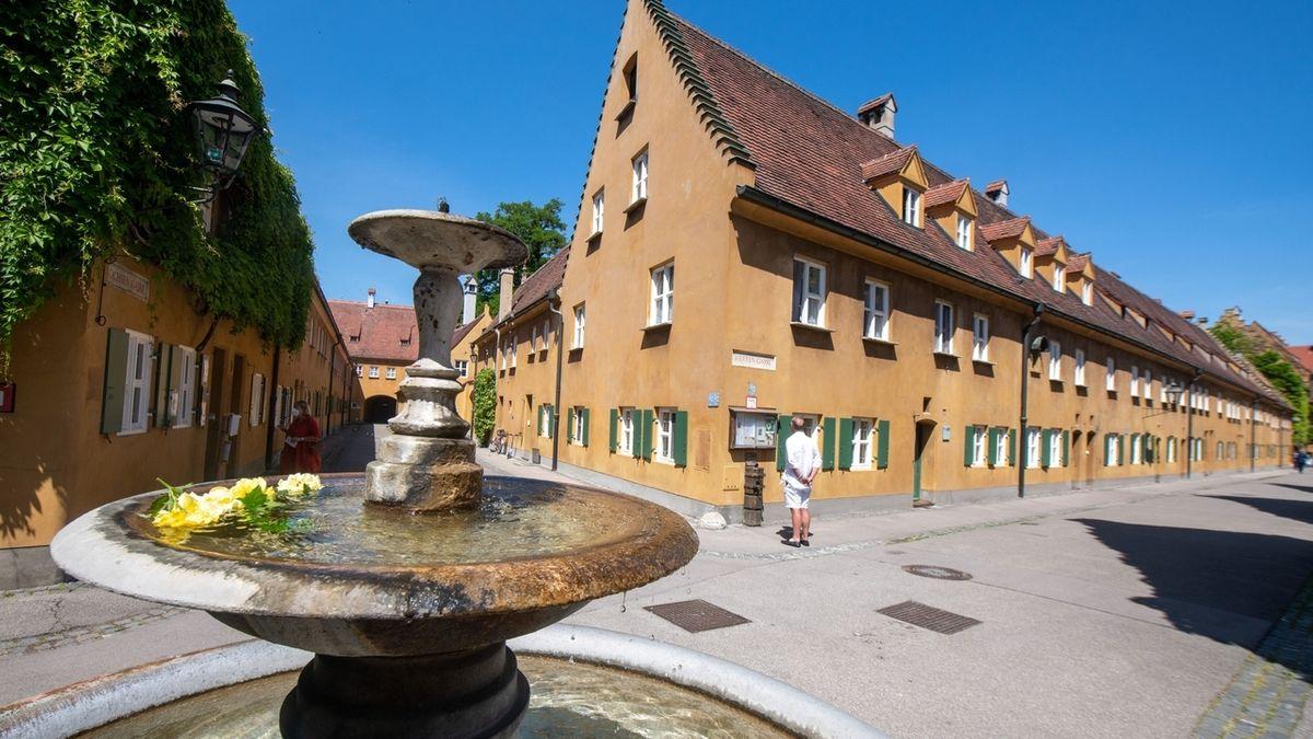 Blick an einem Springbrunnen vorbei auf eines der Giebelhäuser in der Fuggerei in Augsburg