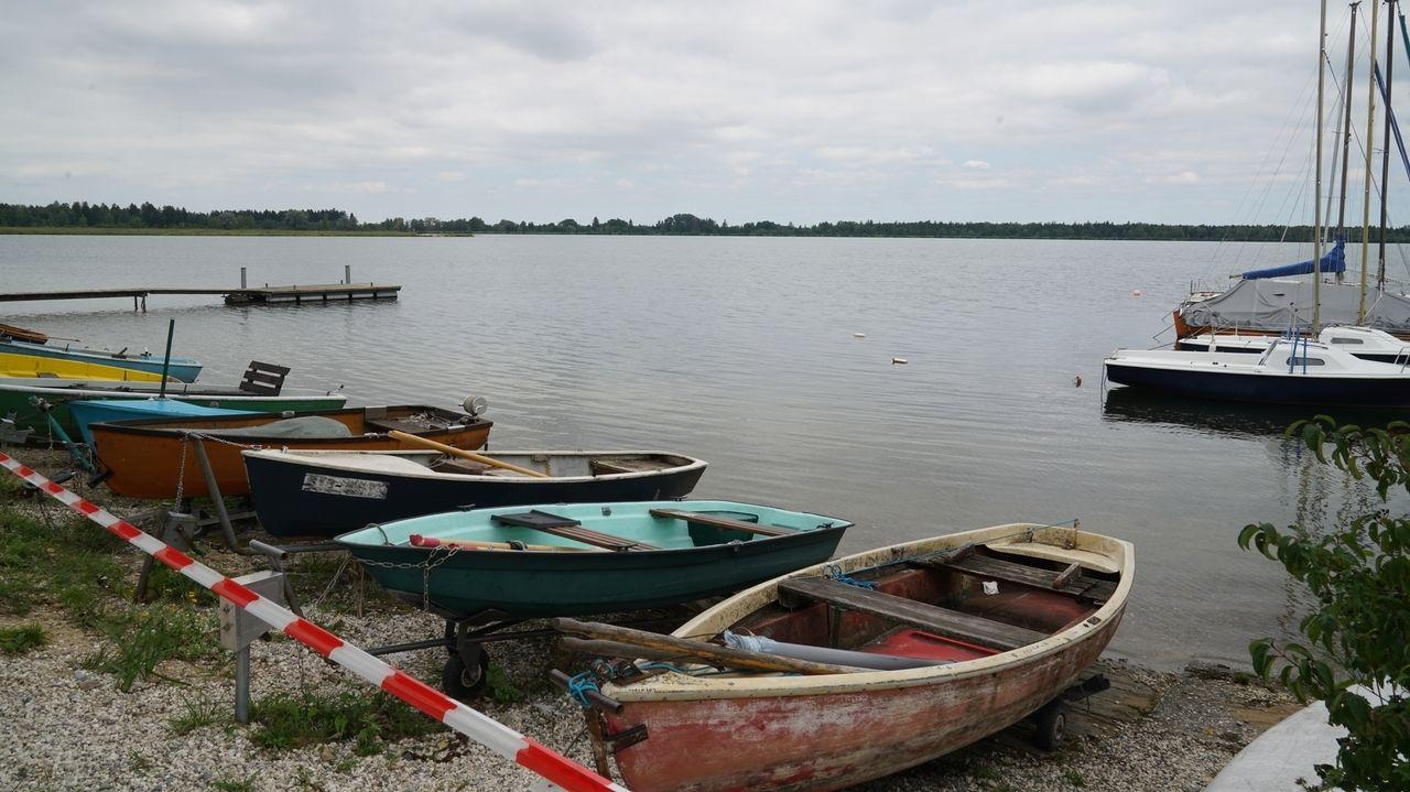 Ein Absperrband vor Ruderbooten und Segelbooten am Mandichosee