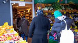 Warteschlange vor einem Gemüse- und Lebensmittelladen. | Bild:pa/dpa/Christian Charisius