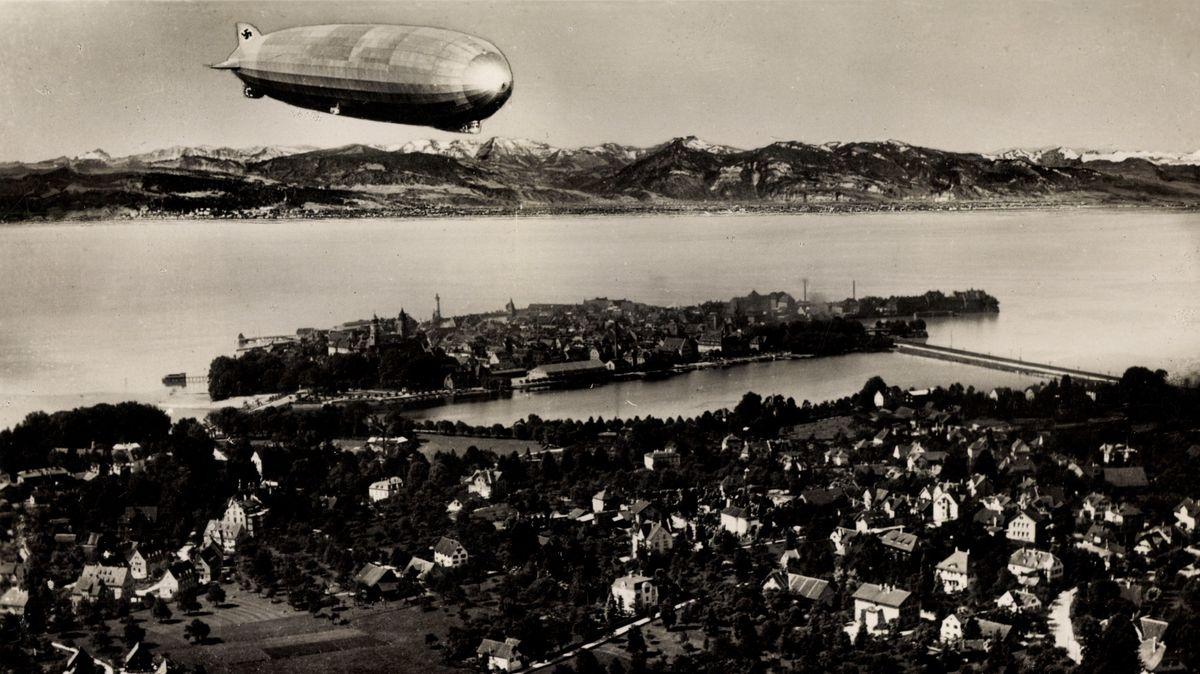 In Schwarz/Weiß: Ein Zeppelin überfliegt die Stadt Lindau. Im Hintergrund: Die Alpen.
