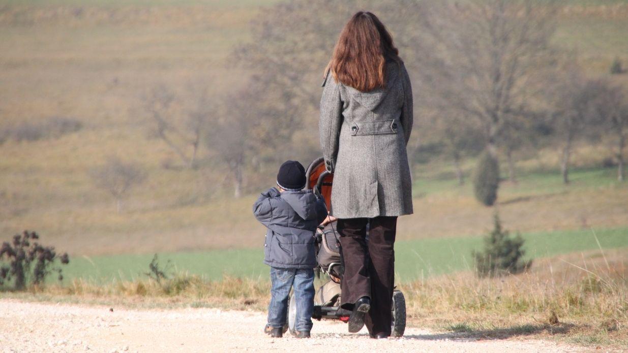 Eine Mutter geht mit einem Kleinkind und einem Baby im Kinderwagen spazieren.