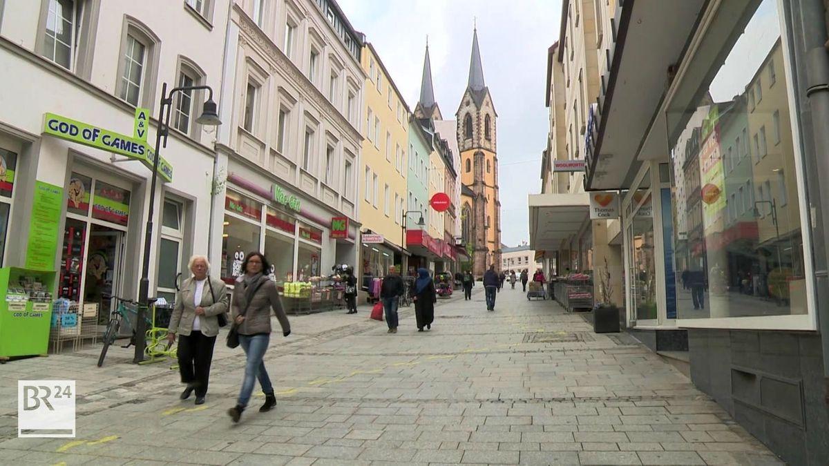 Passanten gehen durch die Fußgängerzone in Hof, im Hintergrund die Kirche mit ihren zwei Türmen.