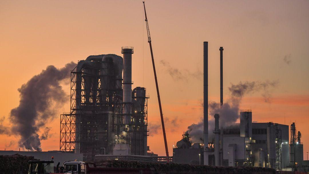 Eine große Industrieanlage mit dampfenden Schornsteinen.