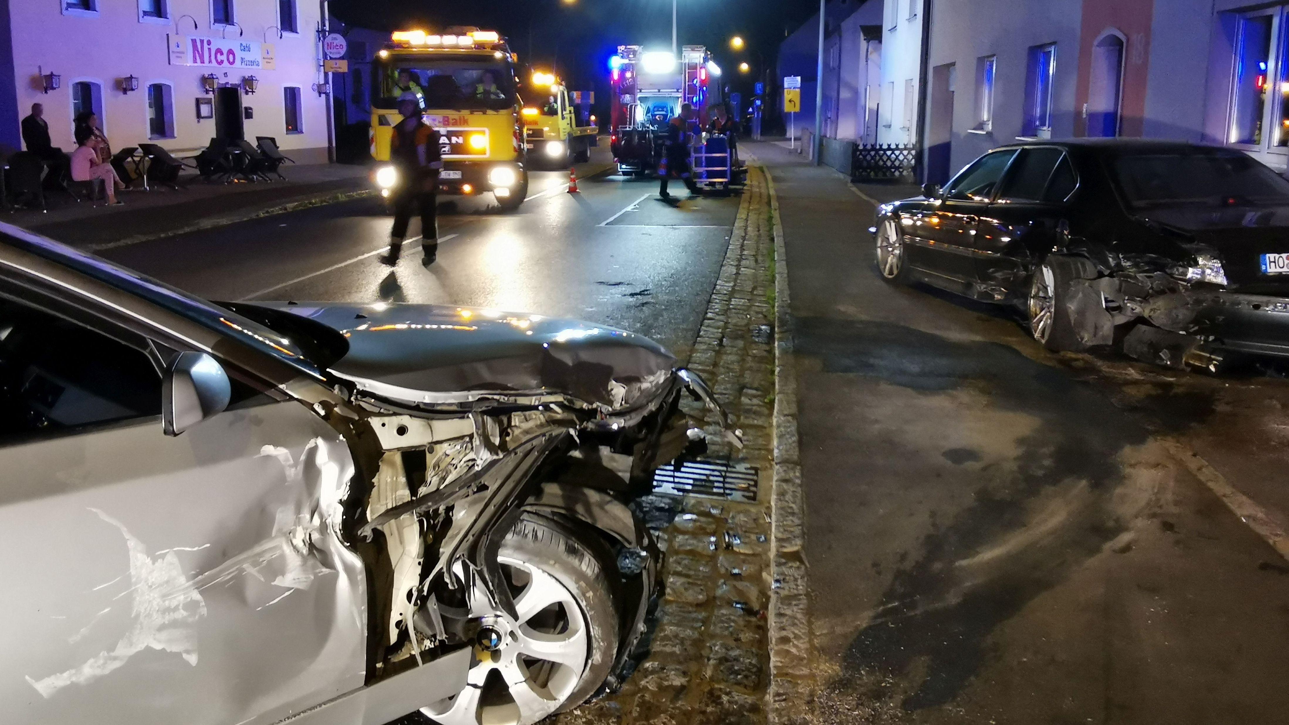 Ein BMW hat einen parkenden Wagen gerammt und gegen eine Hauswand gedrückt