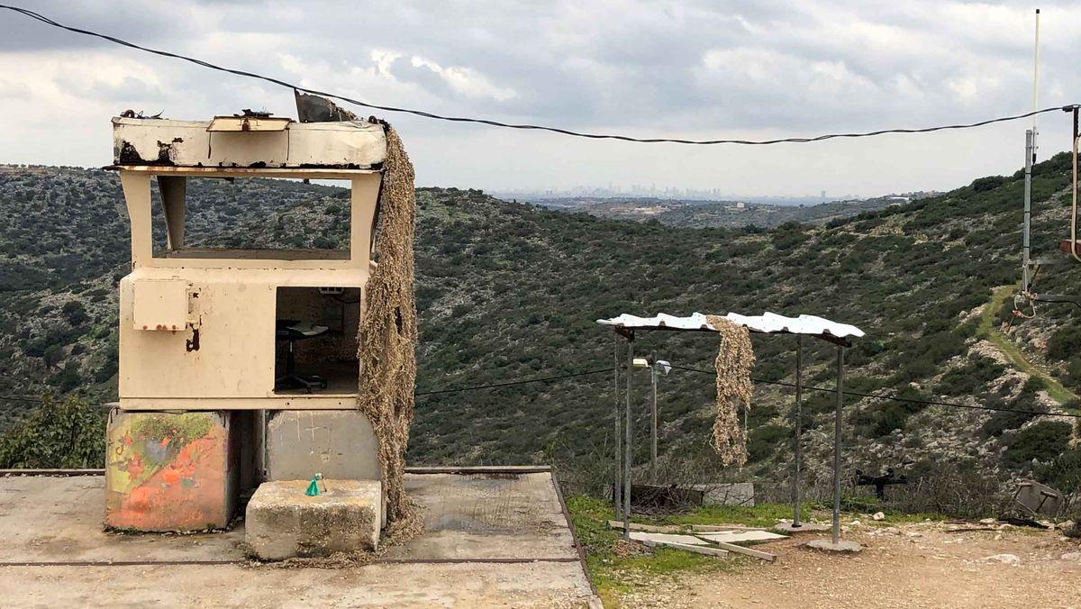 Ein militärisch aussehender Wachposten einer jüdischen Siedlung im grünen Westjordanland. Am Horizont sieht man die Hochhäuser einer größeren Stadt.