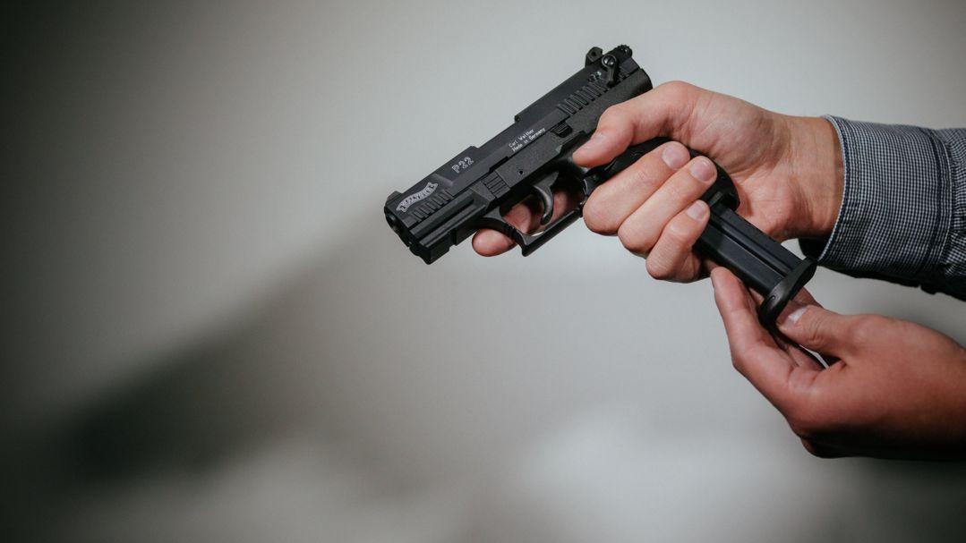 Ein Mann lädt eine Schreckschuss-Pistole Walther P22 mit einem Magazin (Symbolbild)