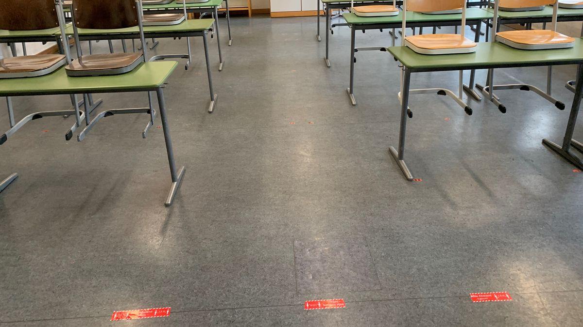 Klassenzimmer mit aufgeklebter Abstandsmarkierung zwischen Schülern und Lehrkraft auf dem Boden.
