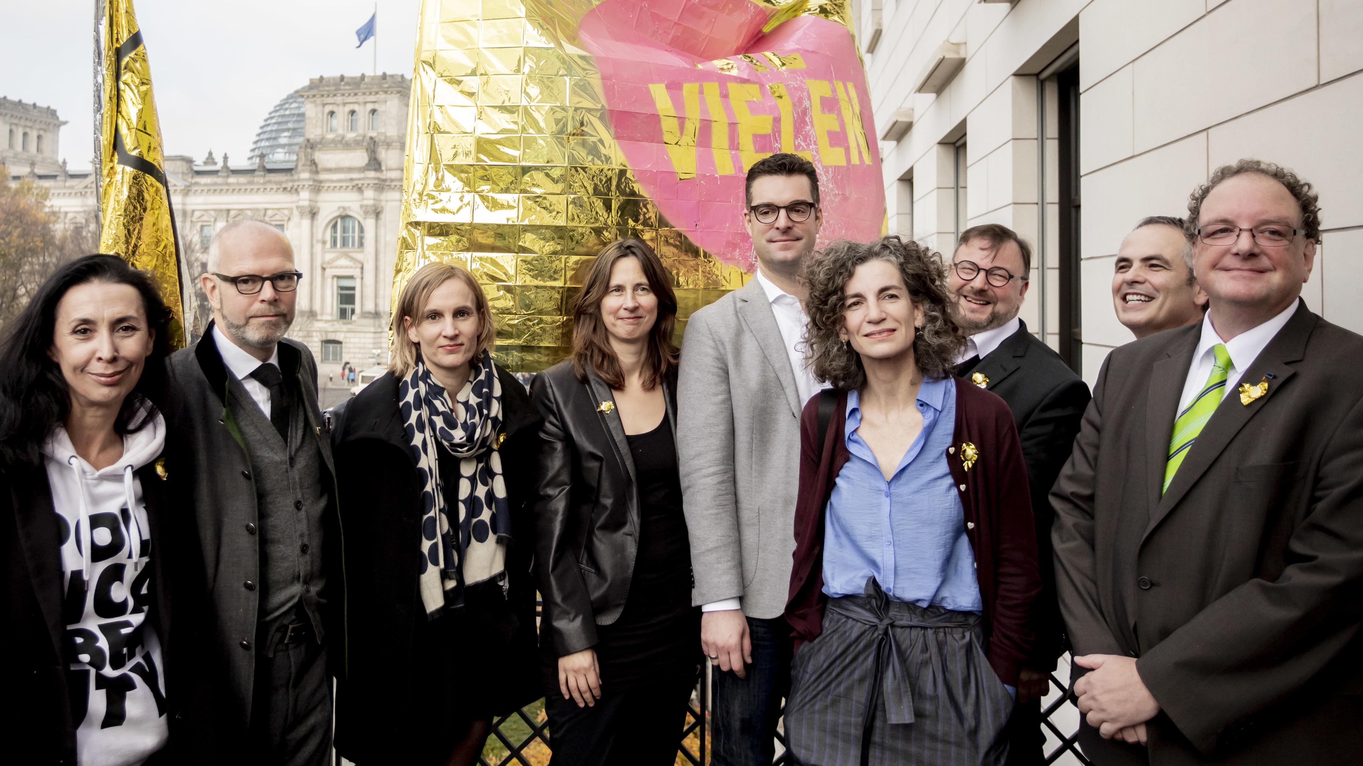 """Unterstützer der Initiative """"Die Vielen"""" bei einer Pressekonferenz in Berlin, hinter ihnen die goldene Flagge der Kampagne und der Bundestag"""