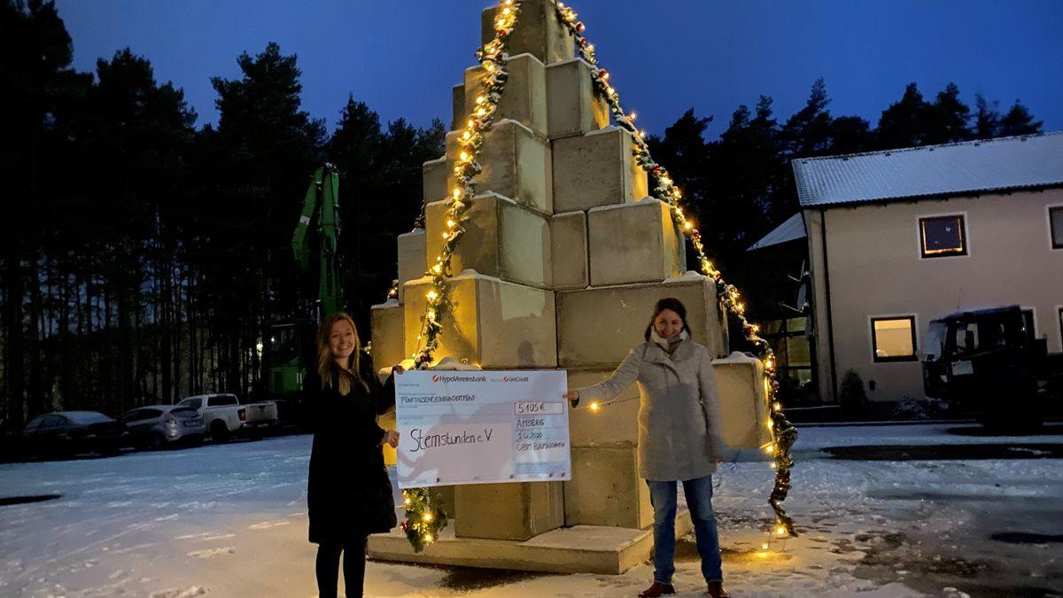 Verantwortliche der Firma OBM Baumaschinen mit einem Scheck vor dem Betonchristbaum